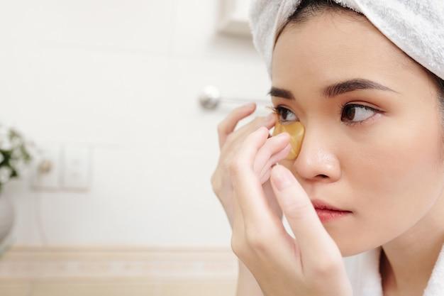 피부에 수분을 공급하고 눈의 원을 없애기 위해 언더아이 패치를 적용하는 젊은 아시아 여성의 클로즈업 이미지