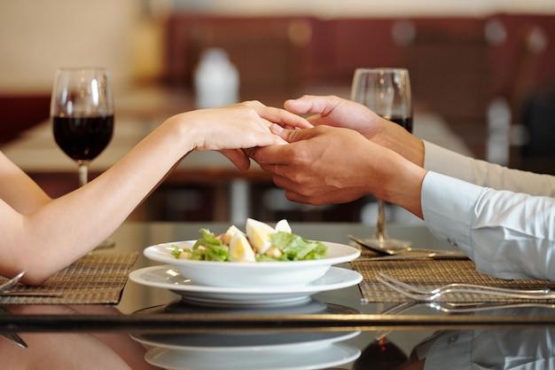 レストランのテーブルの上のサラダのプレートに手をつないでいる若いカップルのクローズアップ画像