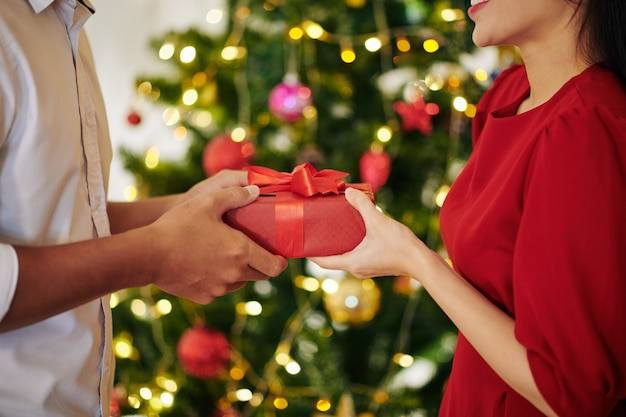 Крупным планом изображение молодого человека, дающего подарок девушке, стоящей у елки