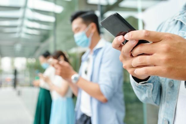 의료 마스크에 야외에서 서서 서로 문자 메시지를 보내는 젊은 사람들의 클로즈업 이미지, 전경에 초점