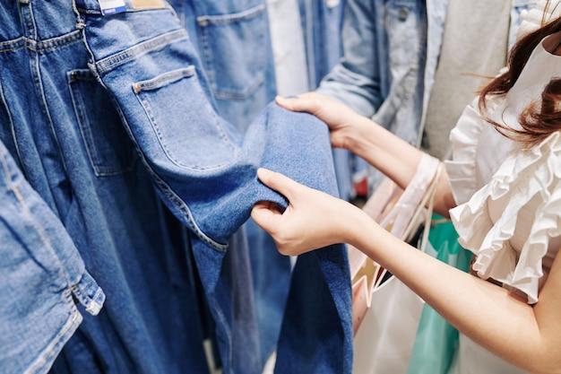 백화점에서 청바지를 선택하는 젊은 여자의 클로즈업 이미지