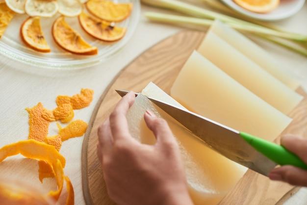 얇은 오렌지와 레몬 조각으로 비누를 만드는 젊은 여성의 클로즈업 이미지