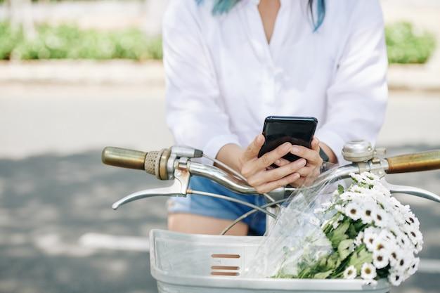 꽃 바구니와 문자 메시지 친구 앞에 자전거에 앉아 젊은 여자의 클로즈업 이미지