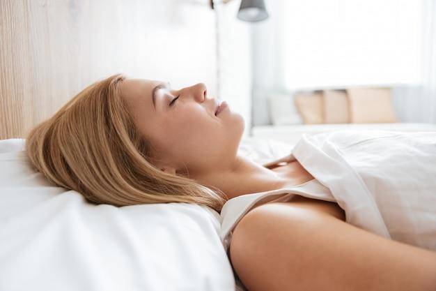 ベッドで寝ている若い女性の画像を閉じる