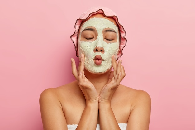 Close up image of pleased woman applies homemade facial mask for dry skin, makes fish mouth, has spa treatment, shows bare shoulders, wears bath cap and towel, cares about appearance, isolated on pink