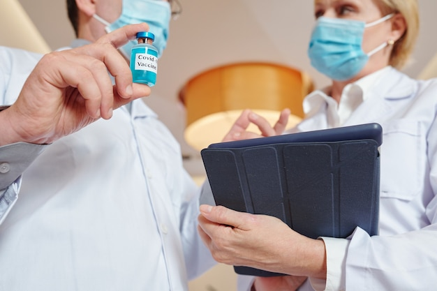 Close-up image of researher with vial and tablet computer discussing process of new vaccine testing
