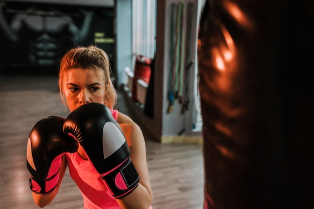 Close-up image of serious boxer girl practicing on a large bag.