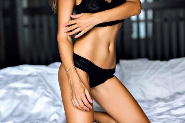 Chiuda sull'immagine della donna sexy che posa sul letto, corpo abbronzato sottile, lingerie nera, goditi il suo stile di vita mattutino, di lusso.