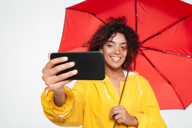 Close up image of smiling african woman in raincoat hiding under umbrella and making selfie on her smartphone over white background