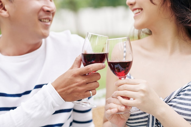 Close-up image of smiling boyfriend and girlfriend drinking red wine when having romantic date outdoors