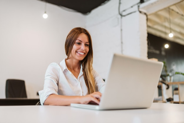 Close-up image of smiling young woman using laptop in bright creative studio.
