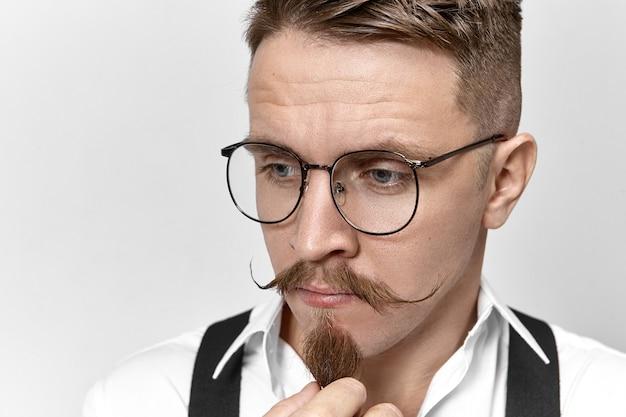 Chiuda sull'immagine dell'imprenditore maschio con la barba lunga pensieroso bello alla moda