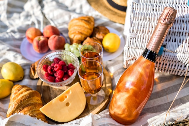 Close up image of tasty food in picnic, sunny colors, cheese fruits bread and champagne, testy breakfast outdoor.
