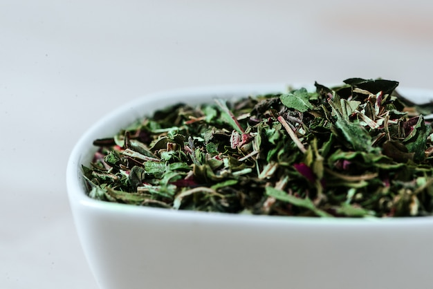 Close-up image of tea leaves in white ceramic bowl.
