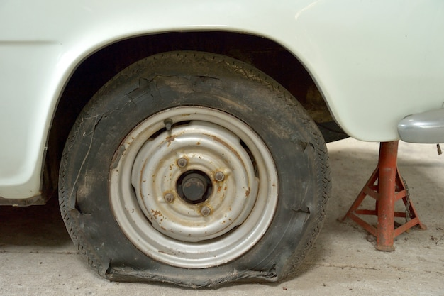 Close-up image of torn tyre on old car.
