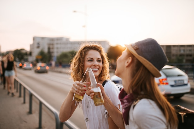 Close-up image of two hipster girls making a toast in the sunset.