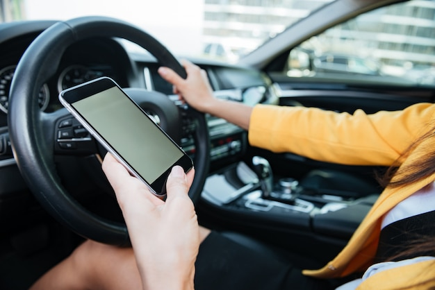 Close up image with female driver and blank phone screen