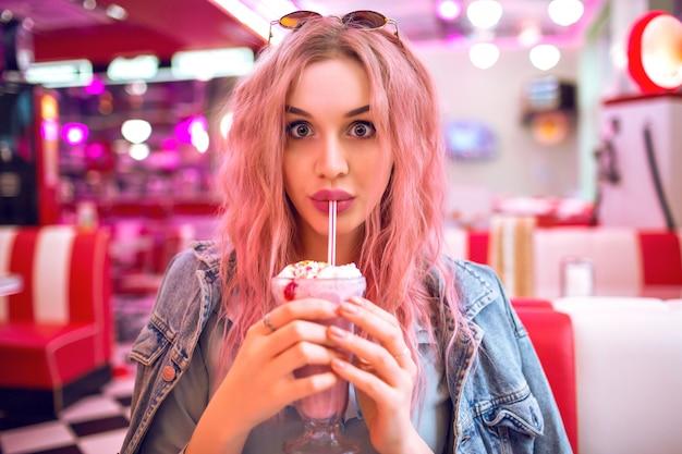 Chiuda sull'immagine della donna che tiene il frappè alla fragola dolce, pin up stile retrò, colori pastello, caffè americano vintage.