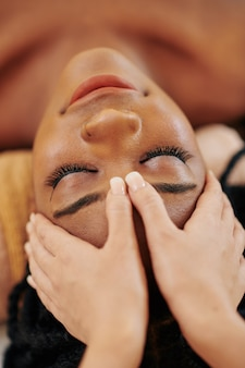 Close-up image of young african-american woman receiving professional head and face massage at spa salon