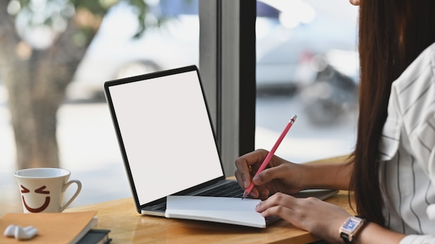 Close-up image of young beautiful confident girl taking notes in front of white blank screen laptop on the wooden cafe bar. modern cafe concept.
