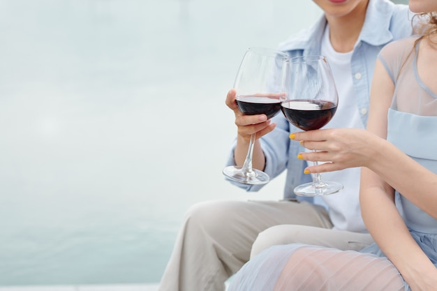 Close-up image of young couple having romantic date and drinking red wine