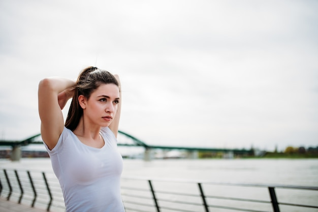 Close-up image of young fitness woman stretching at city quay.