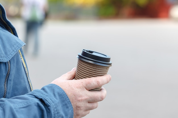 Close-up image of young hipster man walking city streets and drinking coffee to go outside, man wearing casual hoodie and enjoying his cappuccino