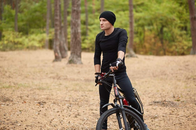 Close up image of young man standing near his bike on forest road, stops to have rest, riding bike on weekends, spending free time