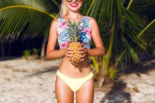 Chiuda sull'immagine di giovane donna slim fit sul bikini che tiene grande ananas dolce e gustoso, stile tropicale di vacanza, palme intorno.