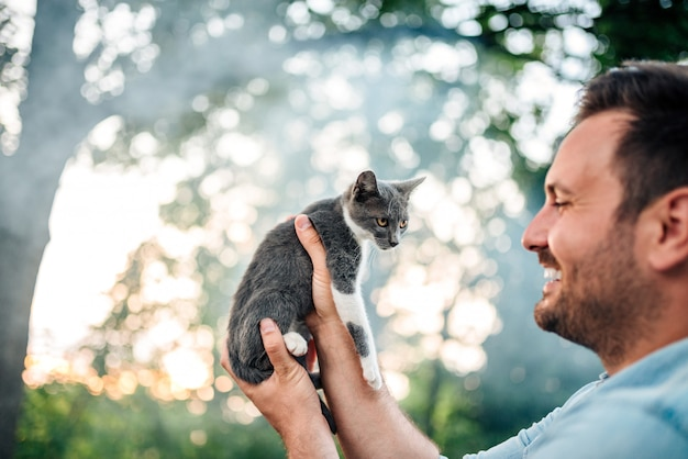 Close-up image of young smiling man holding a small cat outdoors.