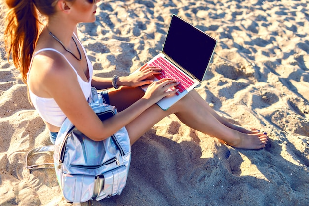 Close up image of young woman sitting on the beach and working on her laptop, backpack, freelance style. work on vacation.