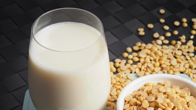 Close-up images of home made healthy drink soy milk with no sugar added in a glass on a green color plastic plate mat and soy beans in small bowl. all of them on black surface