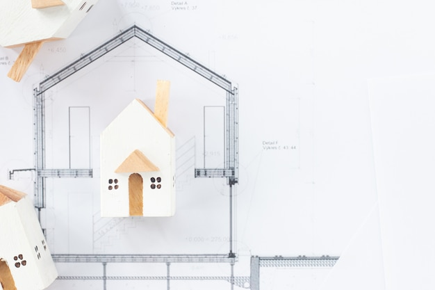 Close up images of miniature white houses on architectural blueprint paper with copy space for message