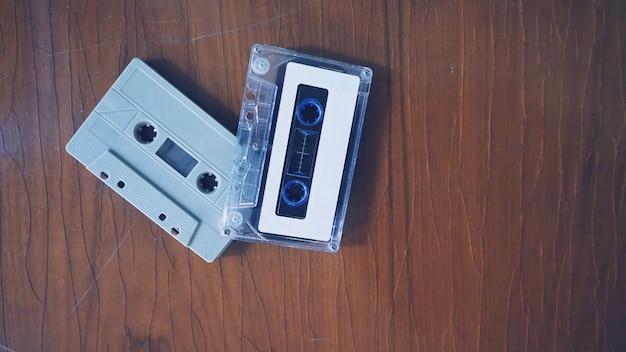レトロな木製テーブルのカセットテープのクローズアップ画像。コンパクトで便利なデバイステクノロジーで録音されたオーディオ音楽や曲のほとんどが80年代または90年代に懐かしい気分や瞬間を表しています。