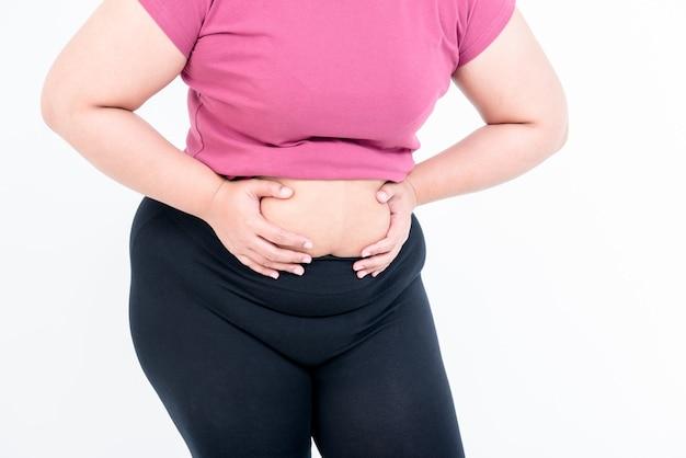 뚱뚱한 여자와 건강 관리 개념에 흰색 배경에 자신의 크기가있는 배꼽 지방을 파악하기 위해 양손을 사용하는 뚱뚱한 여자의 이미지를 닫습니다.