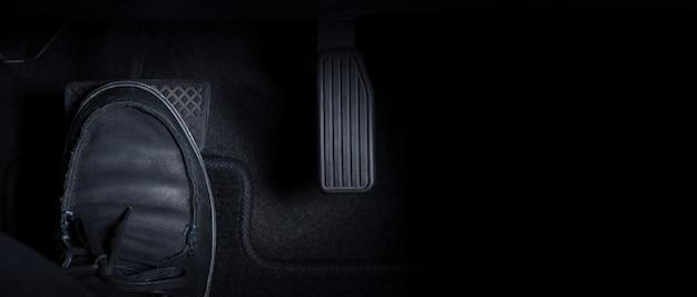 오른발 검은 색 가죽 신발과 검은 색 진 바지로 가속기와 브레이크 페달을 눌러 자동차를 운전하는 사람의 이미지를 닫습니다. 일본 차 안에서.