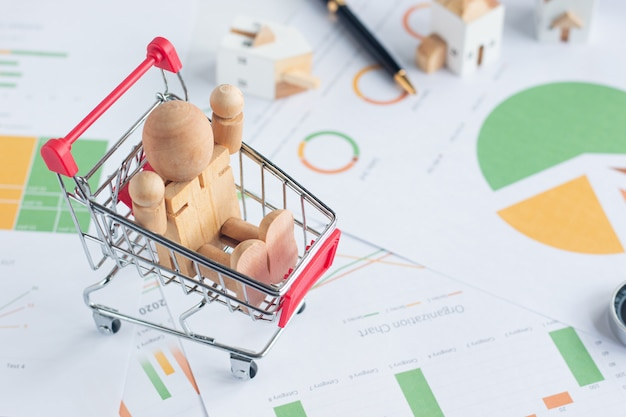 Close up images of wooden mannequin sitting in red shopping cart on financial documents