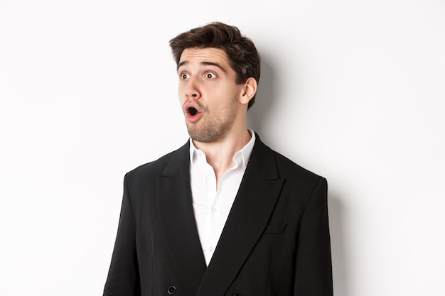 Close-up of impressed guy in trendy suit, open mouth and looking left wondered, standing against white background