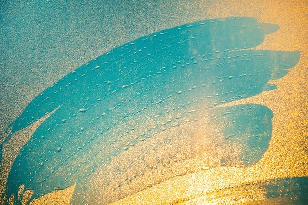 물 먼지가 뿌린 창에 손가락의 클로즈업 인쇄물. 빛나는 일몰 빛의 주황색 음영과 혼합된 파란색 음영. 삽화, 콜라주에 이상적인 배경입니다. 예술적 리터칭.