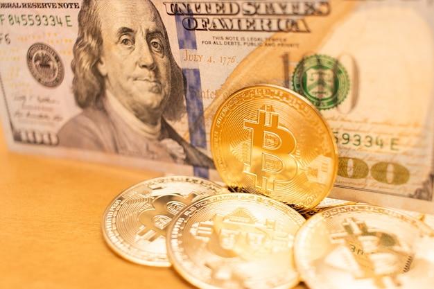 ビットコインコインでクローズアップ、背景に100ドル紙幣、非常に短い被写界深度