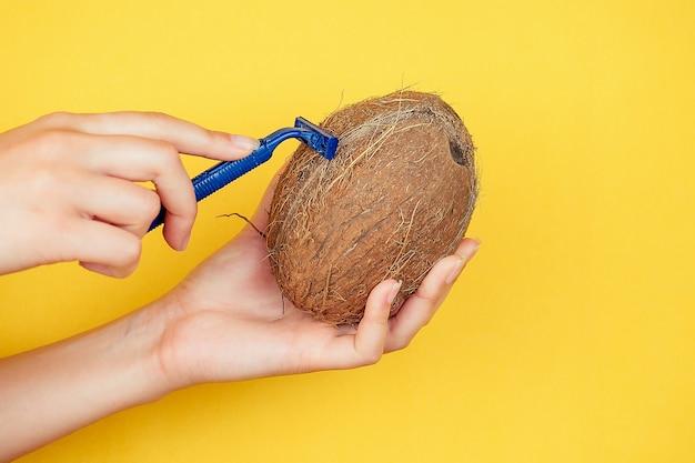黄色の背景にジューシーなフルーツキウイとかみそりを持っている手のひらの上でクローズアップ。体をケアする脱毛と脱毛のアイデア。