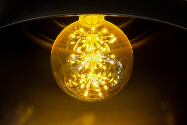 Close up incandescent lamp shining, yellow light of lamp hang on ceiling
