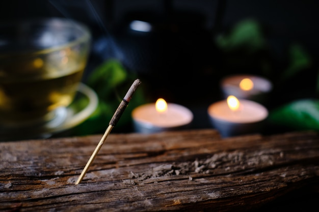 Close-up of incense stick, candles and cup of tea