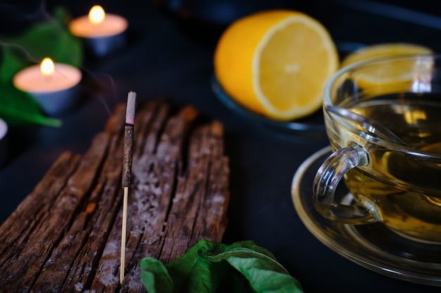 Close-up of incense stick, candles, lemon and cup of green tea