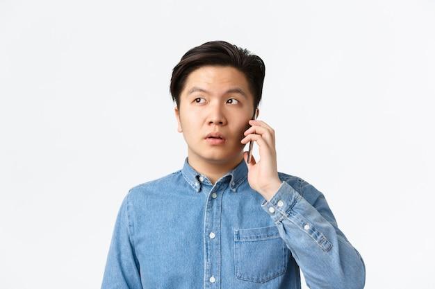 Primo piano di un ragazzo asiatico indeciso che si distanzia durante la telefonata, ha una conversazione e distoglie lo sguardo confuso, in piedi su uno sfondo bianco. uomo che tiene lo smartphone vicino all'orecchio, ordina la consegna del cibo.