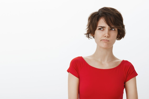 Close-up of indecisive and confused woman pouting, looking upper left corner perplexed