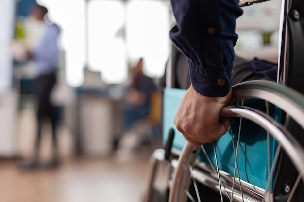 会社のオフィスに入る車椅子の独立した障害者の男性をクローズアップし、同僚に挨拶した後、プロのコンピューターを使用して金融プロジェクトで働き始めて一人で移動します。