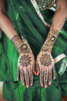 Close-up of indian bride back hand with mehndi (henna tattoo) with beautiful sari
