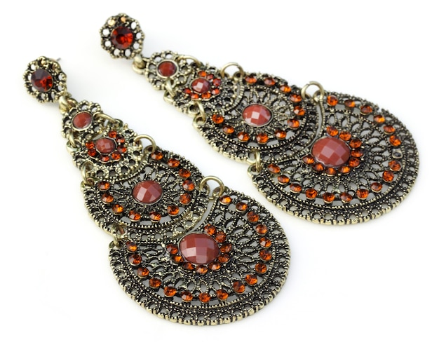 Close up of indian earrings over white background