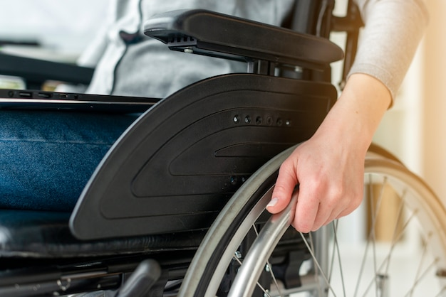 Close-up individual holding hands on wheelchair